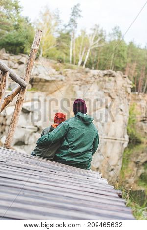 Father And Son Sitting On Wooden Bridge