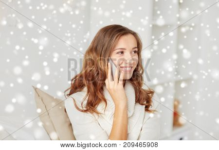 technology, winter, communication and people concept - happy young woman calling on smartphone at home over snow