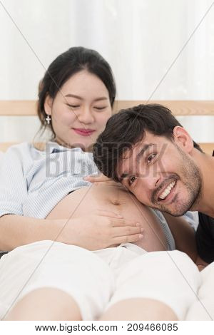 Happiness of Handsome husband is listening to his pregnant wife belly on bed.