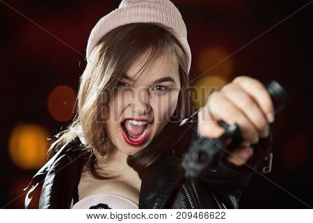 serious girl with gun on blurred background aiming at camera, screaming
