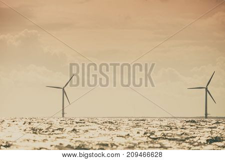 Vertical axis wind turbines generator farm for renewable sustainable and alternative energy production along coast baltic sea near Denmark. Eco power ecology.
