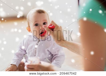 family, food, child, eating and parenthood concept - mother with puree and spoon feeding little baby at home over snow