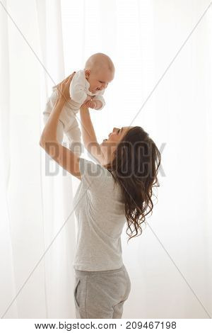Cheerful woman playing with adorable infant child.