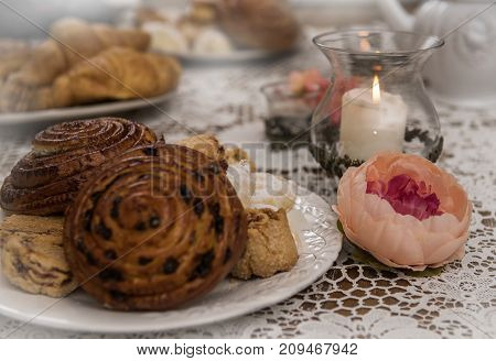 Fresh delicious pastries for breakfast. A candle on the table and a flower.