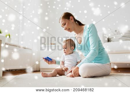 family, technology, child and parenthood concept - happy smiling young mother showing smartphone to little baby at home over snow
