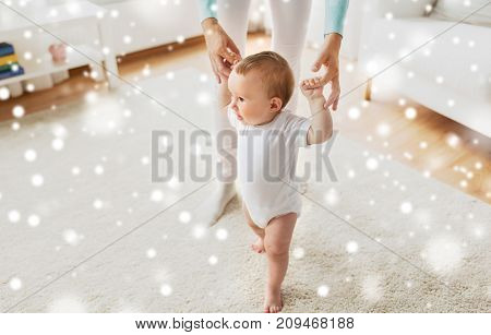 family, child, childhood and parenthood concept - happy little baby learning to walk with mother help at home over snow