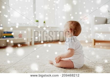 childhood, babyhood and people concept - happy little baby boy or girl sitting on floor at home over snow