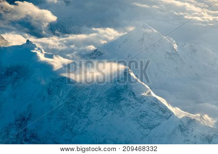 Snow-capped peaks of mountains in the clouds. View from above.