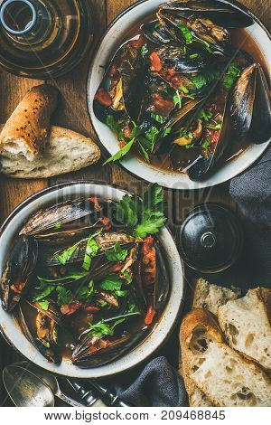 Flat-lay of Belgian boiled mussels in tomato sauce with fresh parsley in serving metal bowls, baguette bread slices and beer in bottle over rustic table background, top view, vertical composition