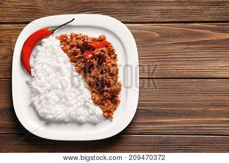 Plate of chili con carne with rice on wooden background