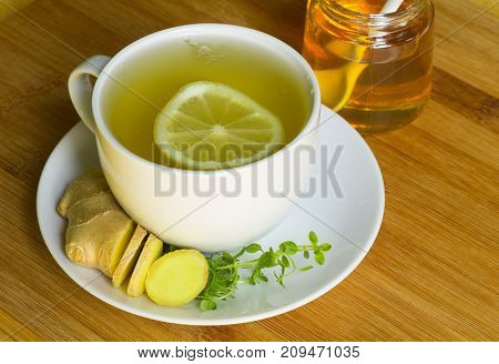 Honey lemon tea in a white cup on a white saucer with fresh sliced ginger, fresh thyme, a lemon slice in tea, and a glass jar of honey in the background.