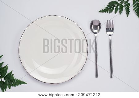 Dinner plate setting top view. Empty plate and silverware set on wooden table