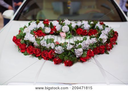 Wedding car and petals on top. Luxury wedding car decorated with flowers.