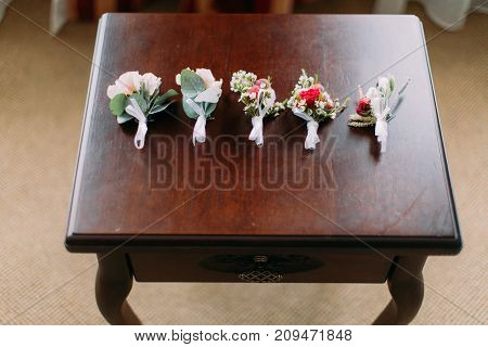 Close-up view of the five boutonnieres of coloutful roses on the table