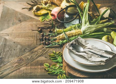 Fall table setting for Thanksgiving day celebration. Plate, cutlery, candle holder, Autumn seasonal vegetables, fruit and fallen yellow leaves for decor over wooden background, copy space