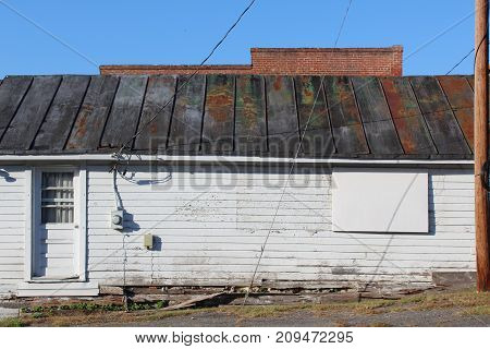 Side view of an old building with patina metal roof and rotting foundation boards