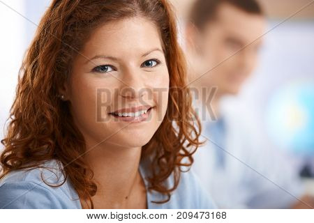 Happy female student in classroom, looking at camera, smiling.