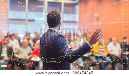 Speaker at business conference with public presentations. Audience at the conference hall. Trough the transparent presentation screen view. Chart can be seen in forground.