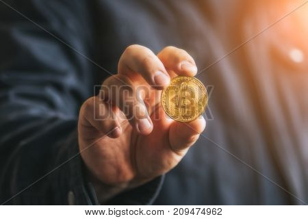 Cryptocurrency golden bitcoin coin in man hand - symbol of crypto currency - electronic virtual money for web banking and international network payment, selective focus, blurred, toned