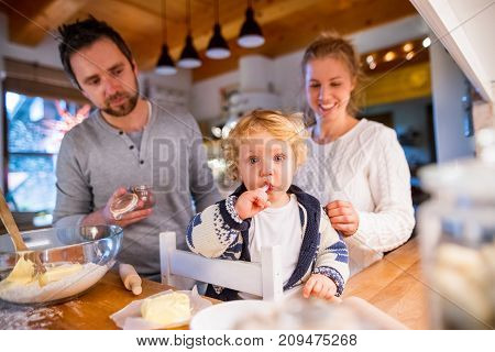 Beautiful young family making cookies at home. Father, mother and a toddler boy baking gingerbread Christmas cookies.