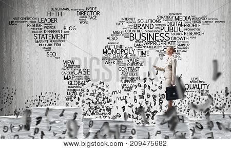 Business woman in suit standing among flying letters with business-related terms in form of world map on background. Mixed media.