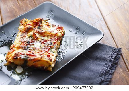 traditional italian lasagna with minced beef bolognese sauce, black modern plate, top view