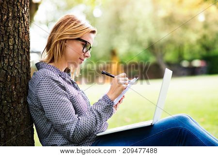 Beautiful young woman studying outdoors. A student with laptop in the garden.