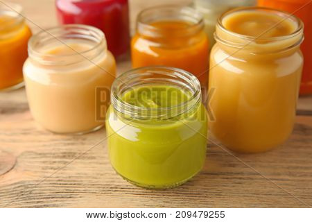 Assortment of jars with tasty baby food on wooden table