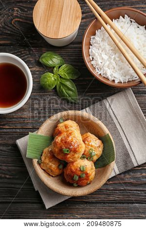 Bowls with delicious meatballs and rice on wooden table