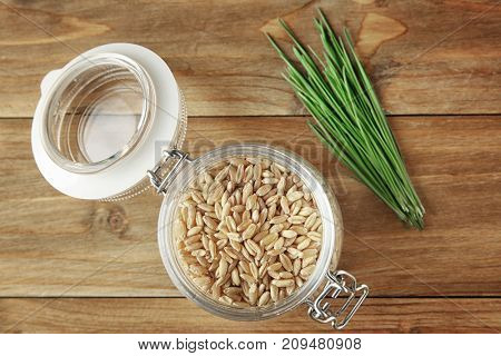 Jar of wheat grass seeds and sprouts on wooden table