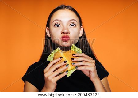 beautiful hungry girl greedily eats up her burger and looks at the camera, isolated, tasty food