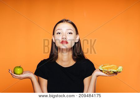 a sad girl chooses that it is better to eat an apple or a mouth-watering sandwich. A girl wants to bite an apple, healthy food, delicious food