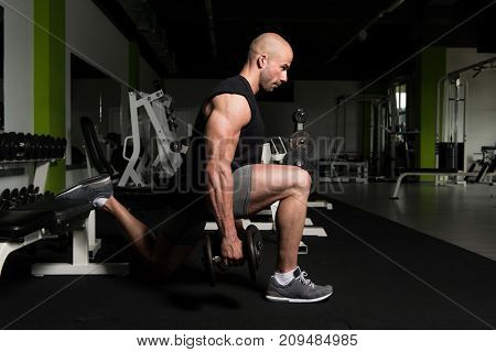 Man Exercising Legs With Dumbbells In The Gym