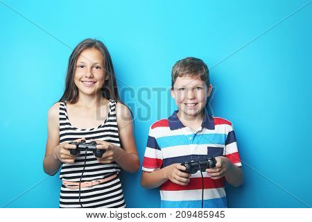 Young boy and girl with joysticks on blue background