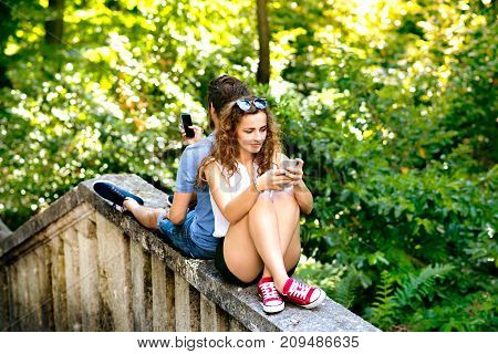 Beautiful young couple in town sitting on concrete wall, holding smart phones, watching or reading something. Sunny spring day.