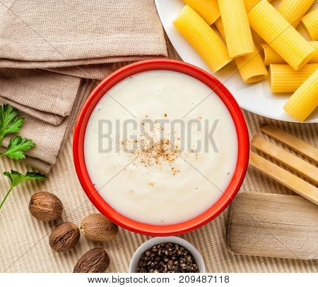 Bechamel white sauce with ingredients utensils and pasta.