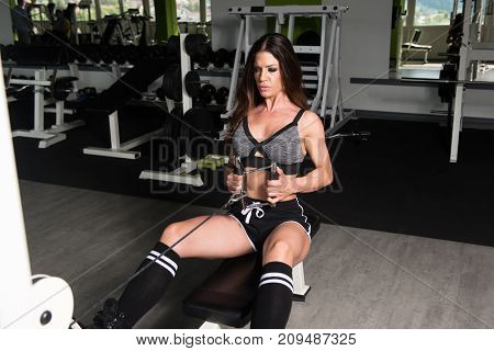Muscular Fitness Woman Athlete Doing Heavy Weight Exercise For Back On Machine With Cable In The Gym