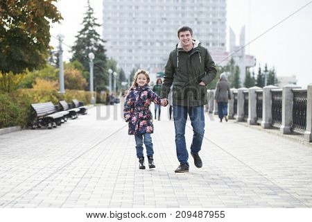 Sundays Father. A young father walks with his daughter in an autumn park