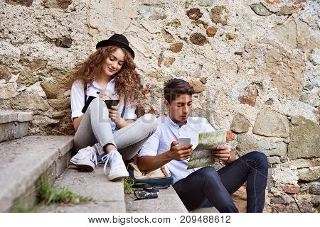Two beautiful young tourists with smartphone, map and camera in the old town. Teenagers sitting on stairs, writting.