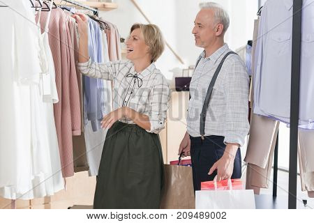 Woman Laughing Near Clothes Rack