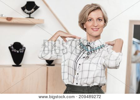 Woman Trying On Necklace At Store