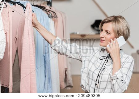 woman talking by smartphone while choosing clothes in a shop
