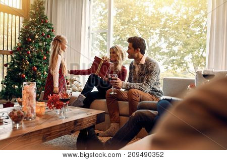 Woman receiving a christmas gift from her little daughter. Happy young family sitting in living room on christmas eve and exchanging gifts.