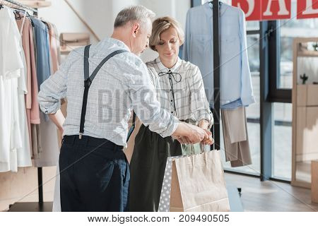Woman Giving Shopping Bags To Man