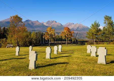 German military cemetery in autumn with  mountains in the background and many graves of soldiers killed in the Second World War.