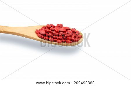 Iron tablets in spoon isolated on white background with copy space for text and clipping path. Use for topics about treatment anemia in adult elderly people and children. Blood donations concept.