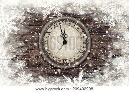 Illustration of vintage clock over wood texture with snow flakes over it. Holiday background. New Year's at midnight