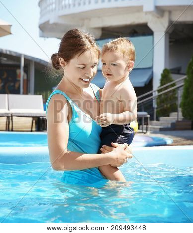 Cute little boy with mother in swimming pool