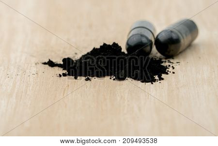 Selective focus on powders of activated charcoal on brown wooden table and blur capsule background
