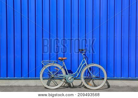 Retro bicycle near blue wall outdoors